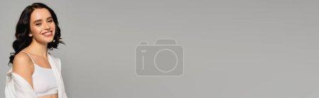 Photo pour Femme brune heureuse en chemise blanche et haut regardant la caméra isolée sur gris, bannière - image libre de droit