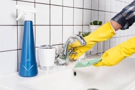 Ausgeschnittene Ansicht einer Frau in Gummihandschuhen, die Lappen in der Nähe von Waschmittel benetzt, auf verschwommenem Vordergrund im Badezimmer