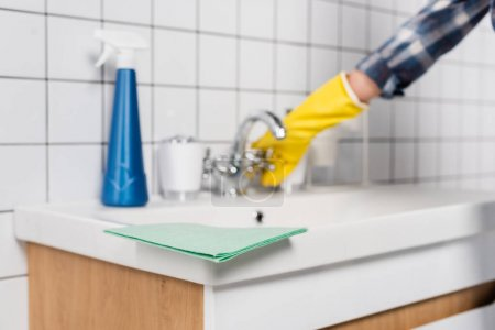 Rag on sink near detergent and woman near faucet on blurred background in bathroom