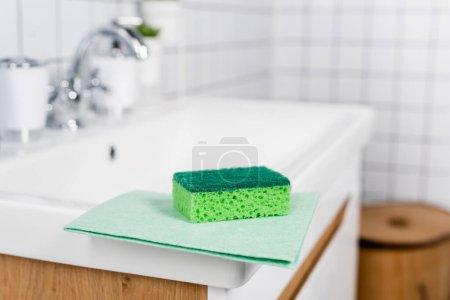 Sponge and rag on sink on blurred background in bathroom