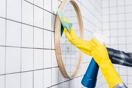 Photo for Cropped view of woman cleaning mirror with detergent and rag in modern bathroom - Royalty Free Image
