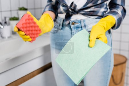 Cropped view of rag and sponge in hands of woman in rubber gloves on blurred background in bathroom