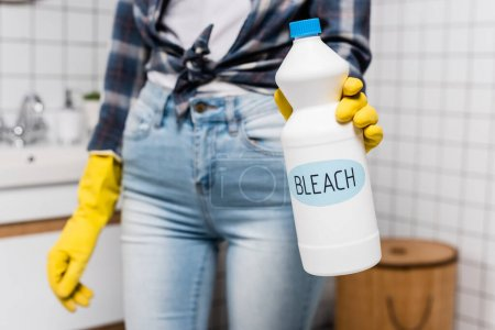 Bottle with bleach lettering in hand of woman in rubber glove on blurred background in bathroom