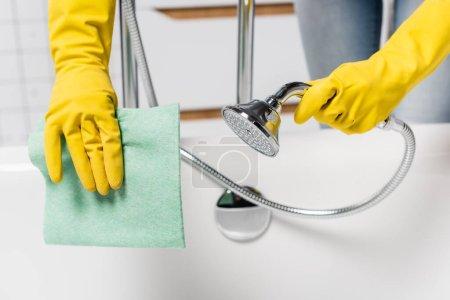 Vista recortada de la mujer en guantes de goma que sostienen la ducha y el trapo en el baño sobre fondo borroso