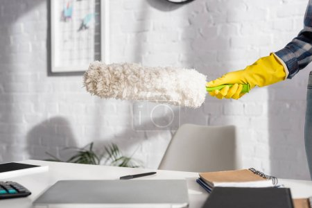Cropped view of woman in rubber glove holding dust brush near devices and notebook on blurred foreground on table