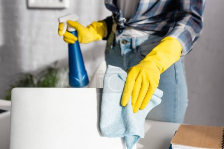 Cropped view of woman in rubber gloves cleaning laptop with rag and holding detergent on blurred background
