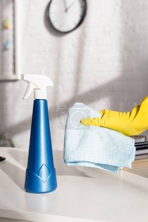 Ausgeschnittene Ansicht der Hand im Gummihandschuh, der Lappen in der Nähe einer Flasche Waschmittel auf dem Tisch hält