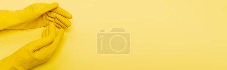 Photo pour Vue du dessus des mains en gants de caoutchouc sur fond jaune, bannière - image libre de droit