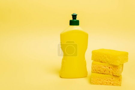 Yellow sponges and bottle of dishwashing liquid with cap on yellow background