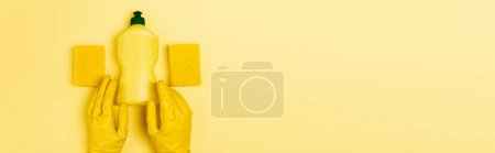 Top view of dishwashing liquid and sponges near hands in rubber gloves on yellow background, banner