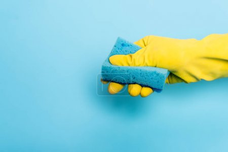 Cropped view of hand in rubber glove holding sponge on blue background
