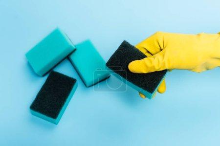 Ansicht der Hand in Gummihandschuhen mit Schwamm auf blauem Hintergrund