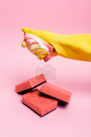 Photo for Hand in rubber glove holding sponge with soapsuds near sponges on pink background - Royalty Free Image