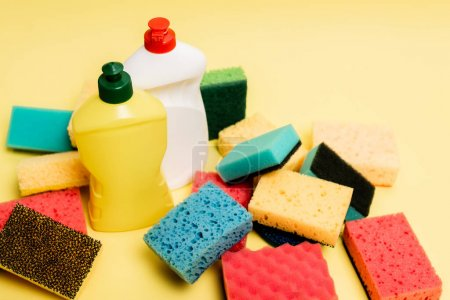 High angle view of dishwashing liquid and sponges on yellow background