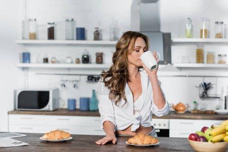 Photo pour Femme sensuelle buvant du café près du petit déjeuner et des fruits sur la table - image libre de droit