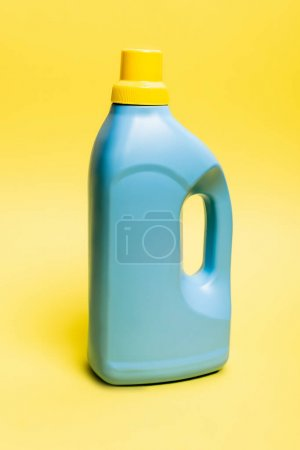 Blue bottle of detergent on yellow background