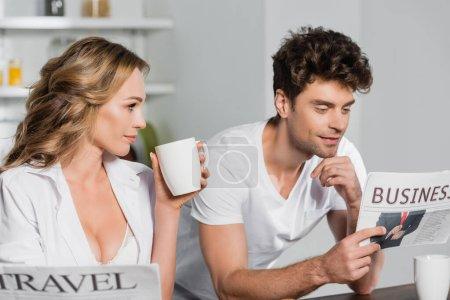 Photo pour Femme sexy avec tasse regardant petit ami lecture journal d'affaires dans la cuisine - image libre de droit