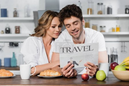 Photo for Smiling man reading travel newspaper near girlfriend and breakfast in kitchen - Royalty Free Image