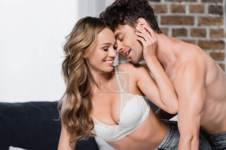 Photo for Smiling man kissing seductive girlfriend in bra at home - Royalty Free Image