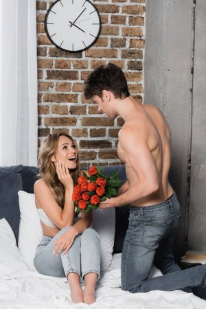 Shirtless man holding roses near amazed girlfriend in bra and jeans on bed