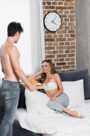 Lächelnde Frau in BH und Jeans schaut Freund mit Frühstückstablett im Schlafzimmer an