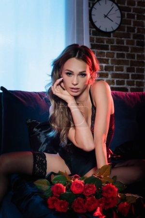 Photo pour Femme sexuelle en body et bas regardant la caméra près des roses sur le premier plan flou sur le lit pendant la soirée - image libre de droit