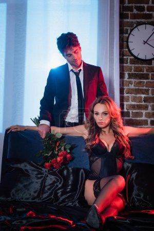 Man in formal wear holding roses near sensual woman on bed