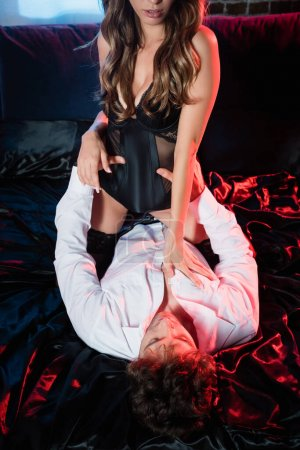 Photo pour Femme sexy en bas et body touchant petit ami en chemise sur le lit - image libre de droit