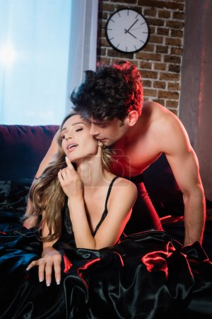 Photo for Muscular man kissing sexy woman on black bedding - Royalty Free Image