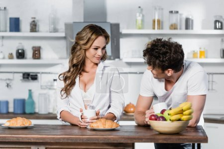 Photo for Sexy woman holding cup and looking at boyfriend near croissants and fruits on blurred foreground - Royalty Free Image