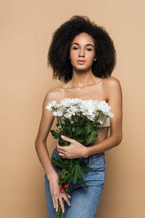 Photo pour Frisée afro-américaine tenant des fleurs isolées sur beige - image libre de droit