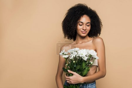happy african american woman holding flowers isolated on beige