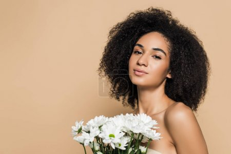 Photo for Curly african american woman with bare shoulders near flowers isolated on beige - Royalty Free Image