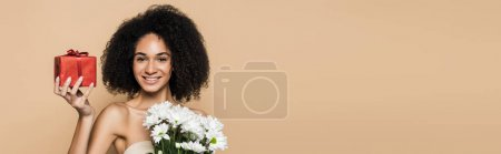 cheerful african american woman with bare shoulders holding present and flowers isolated on beige, banner