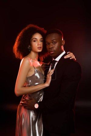 curly african american woman in dress hugging boyfriend in suit on black