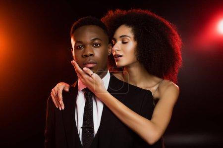 Photo pour Frisé afro-américain femme toucher visage de copain en costume sur noir - image libre de droit