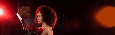 Foto de Mujer afroamericana rizada con rosas rojas cerca de novio en traje en negro, pancarta - Imagen libre de derechos