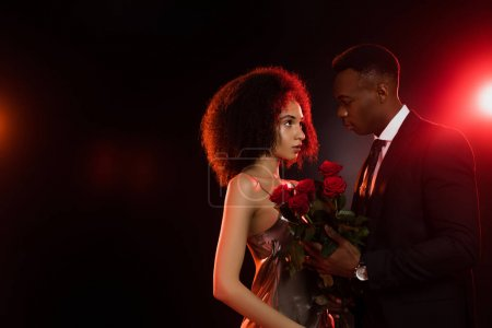 Photo pour Frisé afro-américaine femme avec des roses rouges regardant petit ami en costume sur noir - image libre de droit