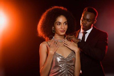 Photo pour Homme afro-américain portant collier sur femme souriante en robe sur noir - image libre de droit