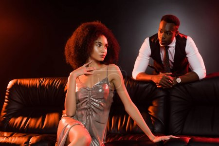 Photo for African american man looking at elegant woman sitting on sofa and black background - Royalty Free Image