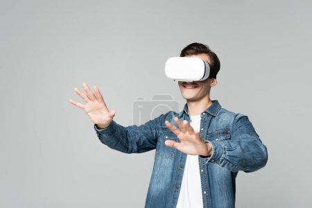Photo pour Homme souriant jouant à un jeu vidéo en réalité virtuelle casque isolé sur gris - image libre de droit