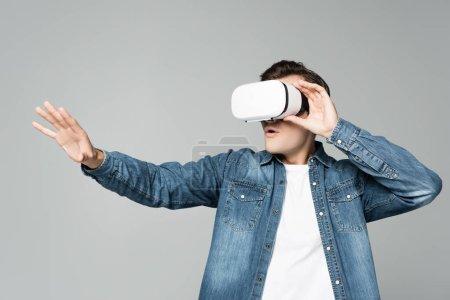 Photo pour Homme excité utilisant casque de réalité virtuelle isolé sur gris - image libre de droit