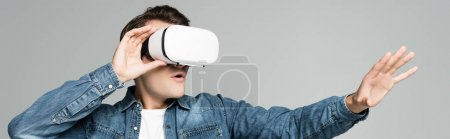 Photo for Young excited man using vr headset isolated on grey, banner - Royalty Free Image