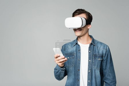 Smiling man vr headset using smartphone isolated on grey