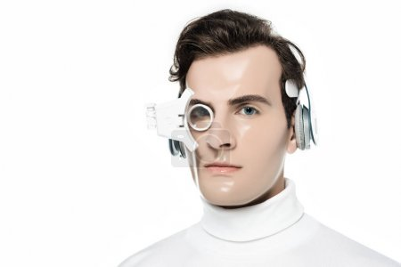 Brunette cyborg man in headphones and eye lens looking at camera isolated on white