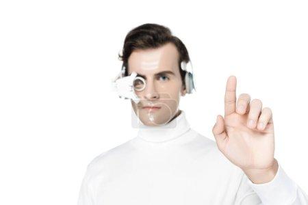 Photo pour Cyborg en lentille oculaire numérique et écouteurs sur fond flou pointant avec doigt isolé sur blanc - image libre de droit