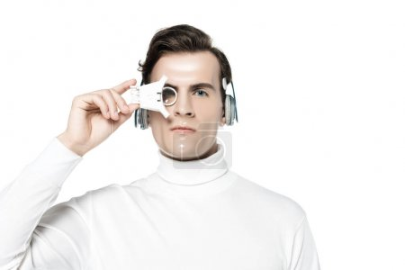 Photo pour Cyborg dans les écouteurs tenant la lentille oculaire numérique isolée sur blanc - image libre de droit