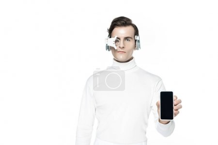 Photo for Cyborg in headphones and eye lens holding smartphone with blank screen isolated on white - Royalty Free Image
