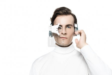 Cyborg in digital eye lens touching headphones and looking at camera isolated on white