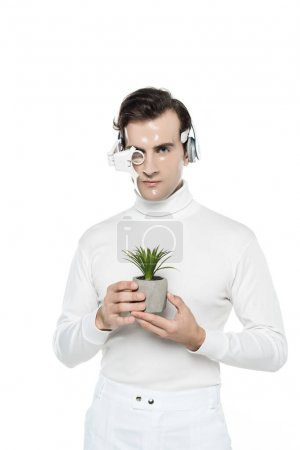 Cyborg man in headphones and digital eye lens holding potted plant isolated on white